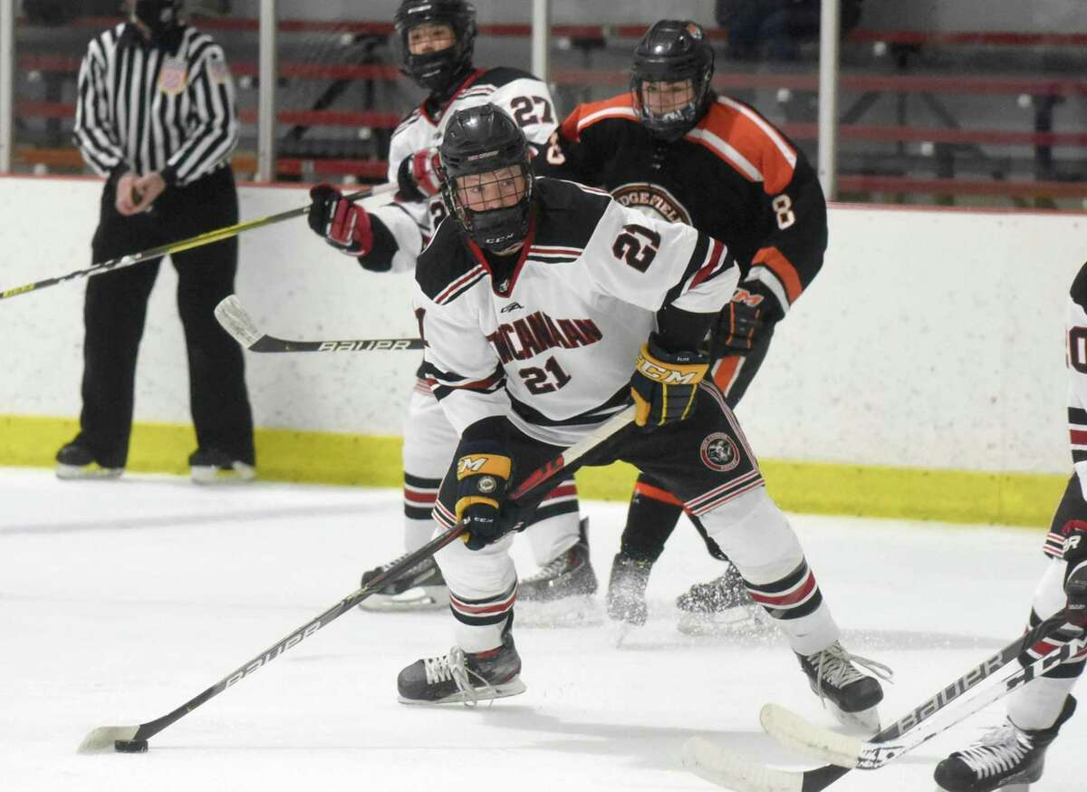 New Canaan's Carter Ellis (21) lines up for a shot during the Rams' boys ice hockey game against Ridgefield at the Darien Ice House on Saturday, Feb. 13, 2021.