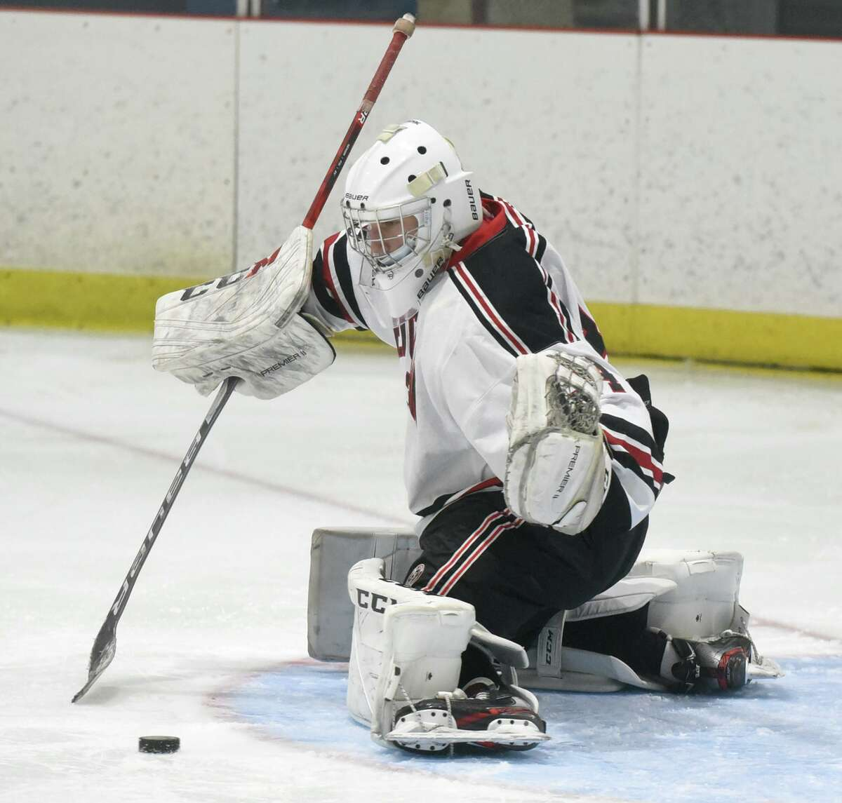 New Canaan goalie Beau Johnson makes a kick save during the Rams' boys ice hockey game against Ridgefield at the Darien Ice House on Saturday, Feb. 13, 2021.