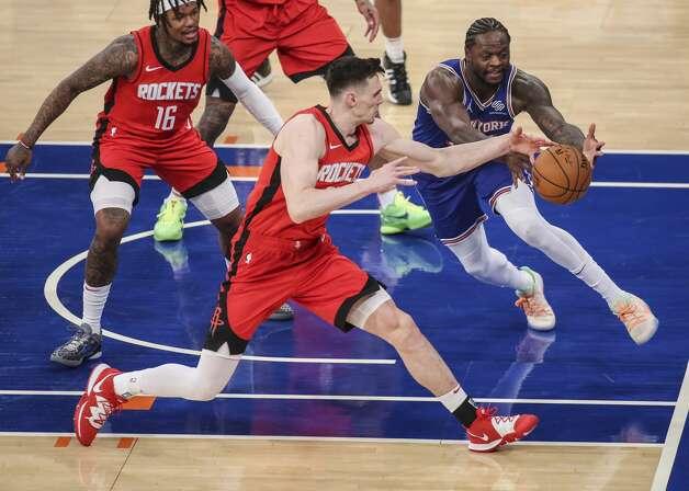 New York Knicks forward Julius Randle, right, and Houston Rockets forward Rodions Kurucs reach for the ball during the fourth quarter of an NBA basketball game Saturday, Feb. 13, 2021, in New York. (Wendell Cruz/Pool Photo via AP) Photo: Wendell Cruz/Associated Press / Wendell Cruz