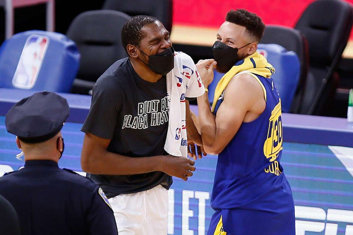 Brooklyn Nets forward Kevin Durant (7) and Golden State Warriors guard Stephen Curry (30) talk and laugh as they meet following the end of the NBA game at Chase Center, Saturday, Feb. 13, 2021, in San Francisco, Calif. The Nets won 134-117.