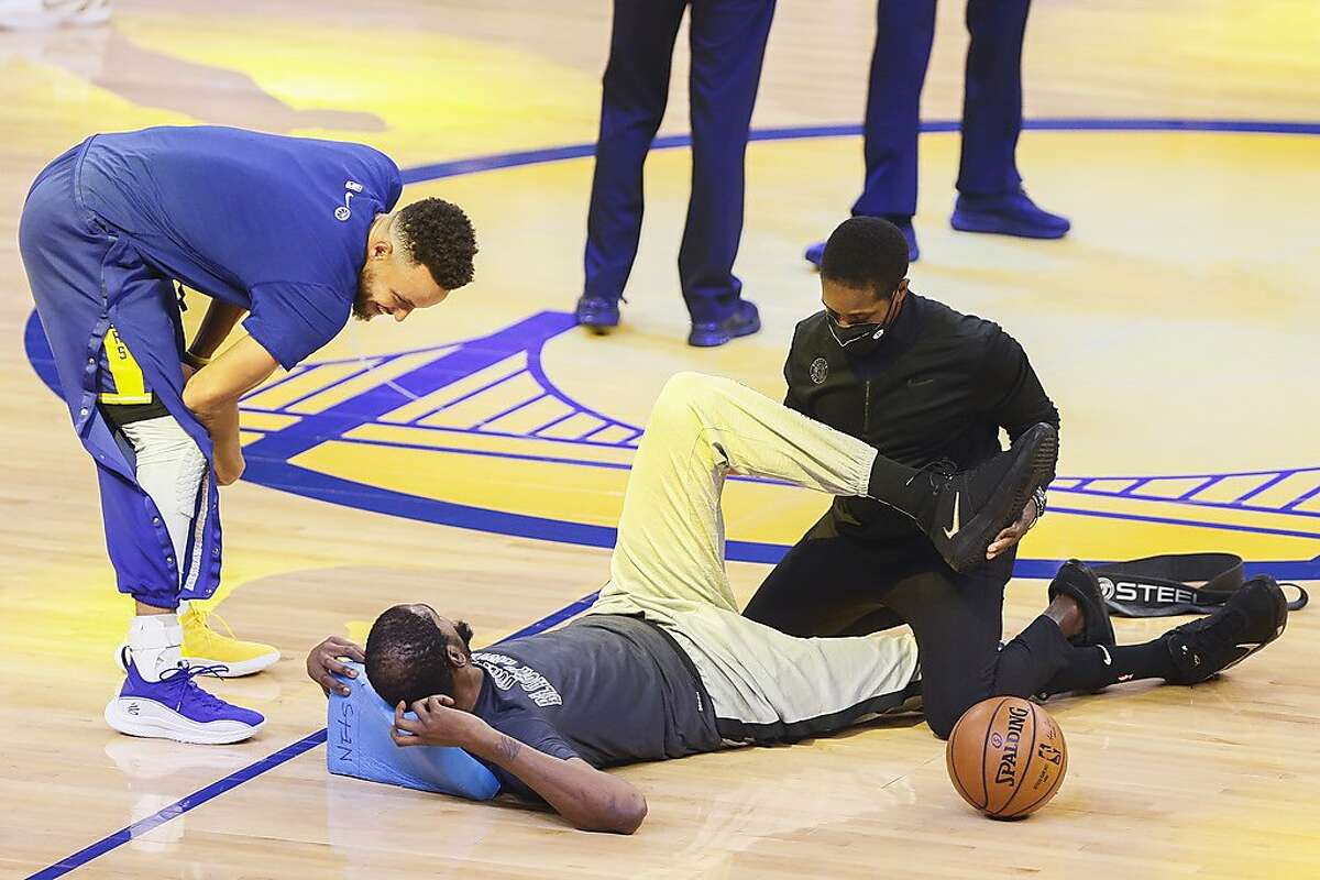 Golden State Warriors guard Stephen Curry (30) walks over and chats with Brooklyn Nets forward Kevin Durant (7) as he stretches before the NBA game at Chase Center, Saturday, Feb. 13, 2021, in San Francisco, Calif.