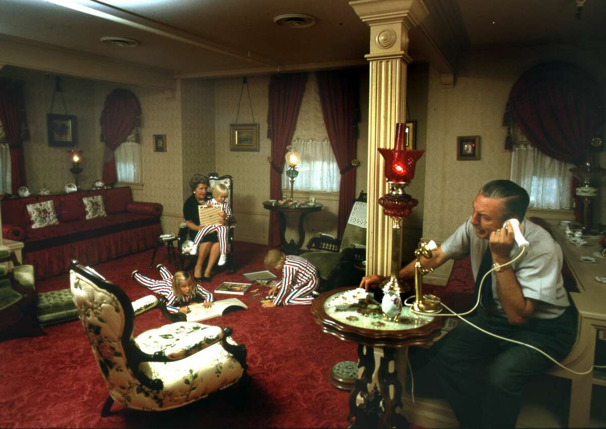 Walt Disney talks on the telephone while his wife, Lillian Disney plays with three of their grandchildren, Joanna, Tamara, and Jennifer, in January 1962. The couple are their apartment above the Disneyland fire station.