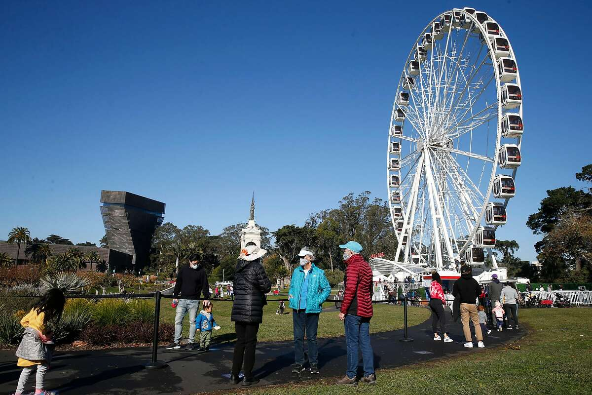 Visitors wear masks and maintain social distancing while waiting in line for a spin aboard the Skystar observation wheel at Golden Gate Park in November.