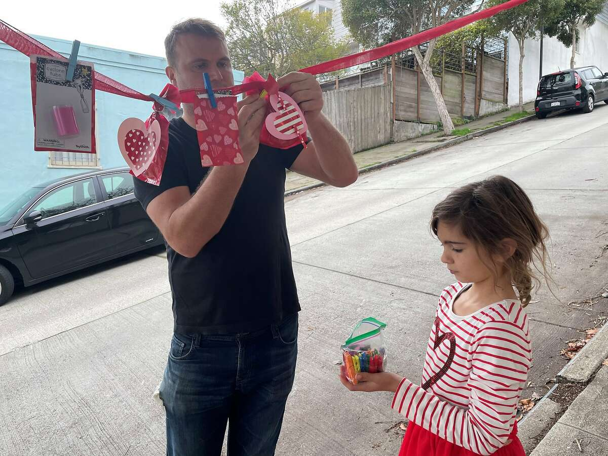 Ryan Butterfoss and his daughter Lilly put up valentines in front of their home before the start of the