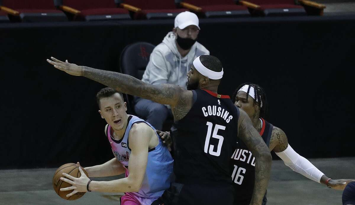 Miami Heat guard Duncan Robinson (55) gets trapped by Houston Rockets center DeMarcus Cousins (15) and guard Ben McLemore (16) during the fourth quarter of an NBA basketball game at Toyota Center, in Houston, Thursday, February 11, 2021.