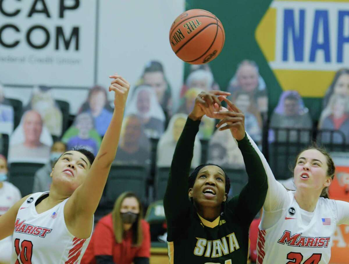Siena's Tobulayefa Watts, center, battles for a rebound against Caitlin Weimar, left, and Sarah Barcello of Marist during their game on Sunday, Feb. 14, 2021, in Loudonville, N.Y. (Paul Buckowski/Times Union)