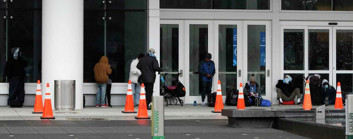 People stand in line outside of the George R. Brown Convention Center, in Houston, Sunday, February 14, 2021, which city officials opened as an emergency shelter for the area homeless, who needed to get out of the freezing temperatures.