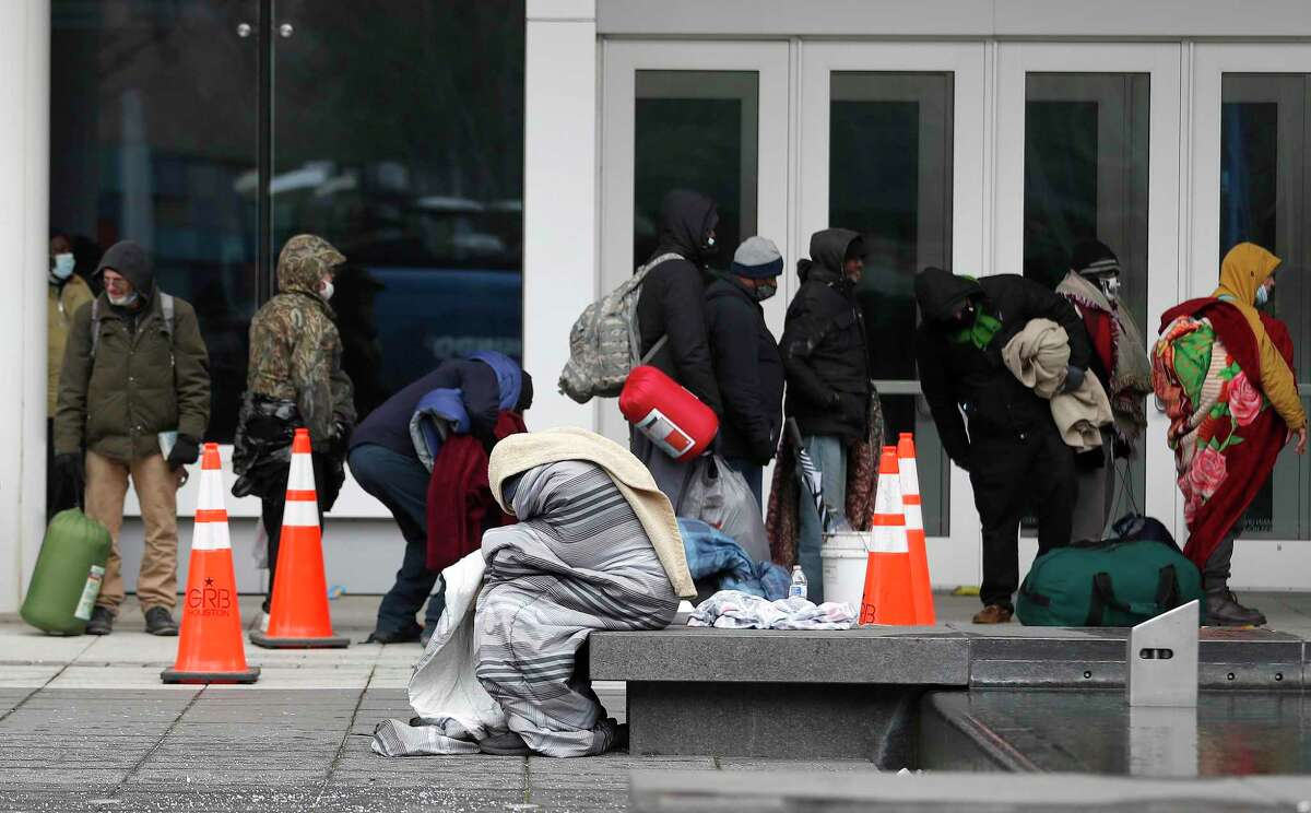A person huddles in layers of blankets near a line of more than 200 people waiting to get into the George R. Brown Convention Center, in Houston, Sunday, February 14, 2021, which city officials opened as an emergency shelter for the area homeless, who needed to get out of the freezing temperatures.