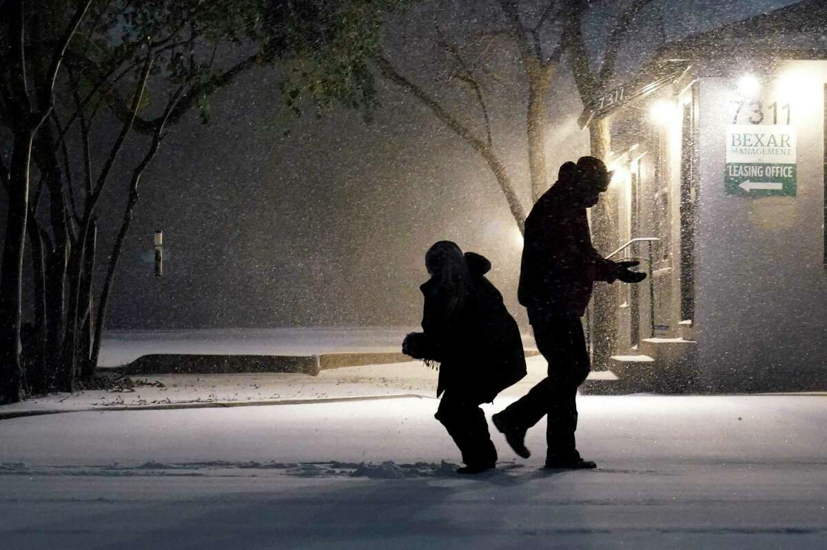 Two people play in the snow in San Antonio, Sunday, Feb. 14, 2021. Snow and ice blanketed large swaths of the U.S. on Sunday, prompting canceled flights, making driving perilous and reaching into areas as far south as Texas' Gulf Coast, where snow and sleet were expected overnight.