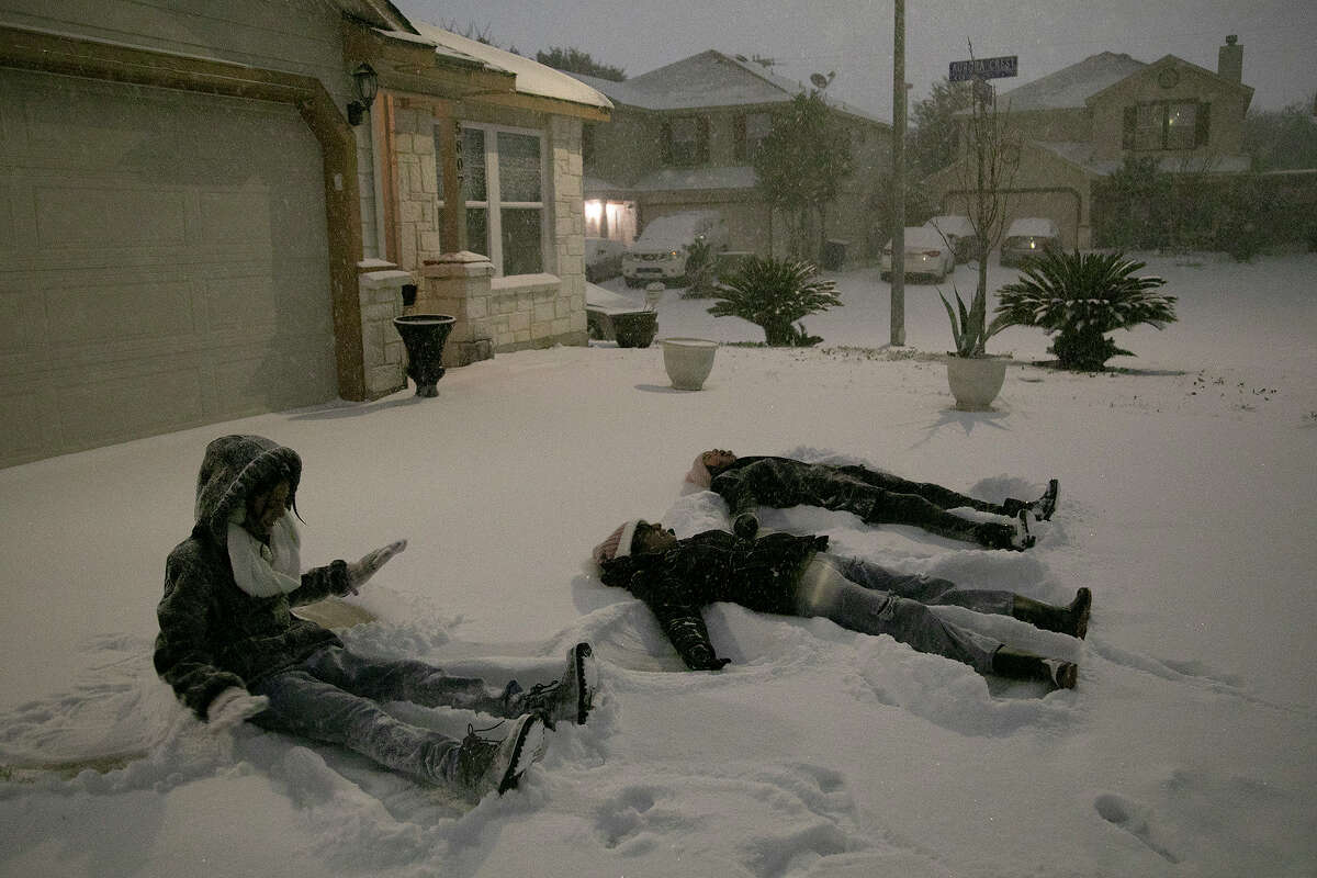 Carmen Rodriguez, 12, from left, her sister, Georgina Rodriguez, 13, and Gaby Gonzalez, 13, make snow angels in their neighbor's driveway late Sunday night, Feb. 14, 2021, in San Antonio.