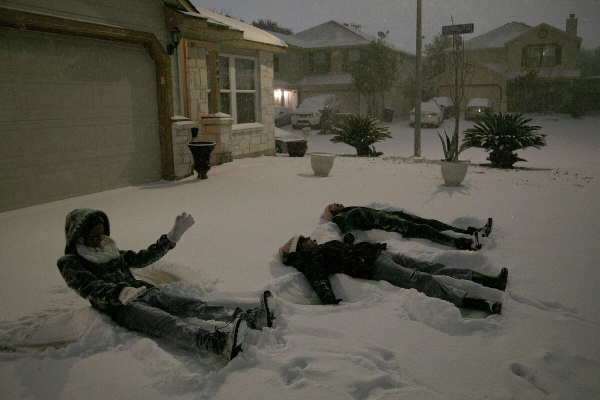 Carmen Rodriguez, 12, from left, her sister, Georgina Rodriguez, 13, and Gaby Gonzales, 13, make snow angels in their neighbor's driveway late Sunday night, Feb. 14, 2021, in San Antonio.
