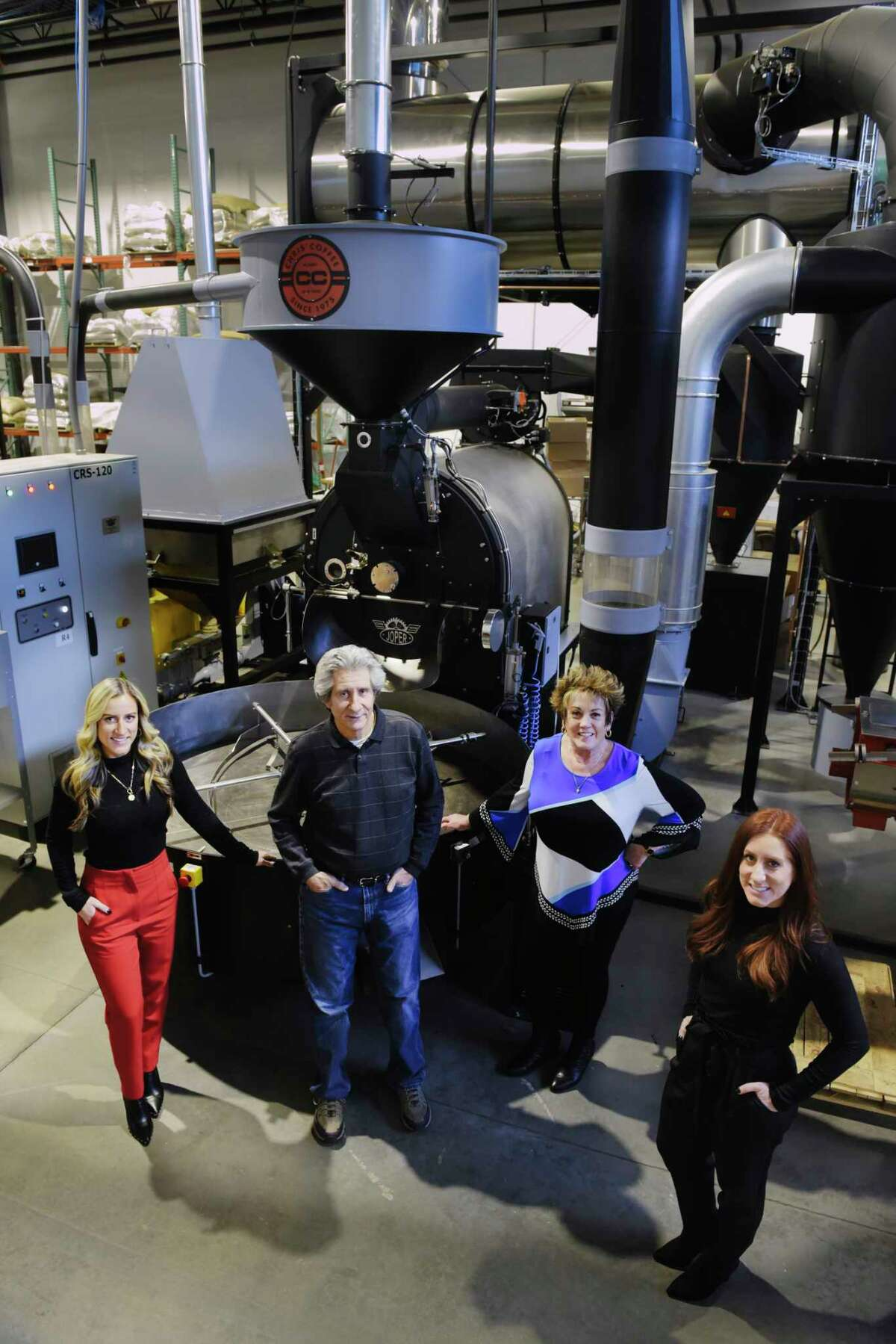 Chris' Coffee family members, Taylor Nachtrieb, left, operations manager, her dad, Chris Nachtrieb, president, her mom, Pat Nachtrieb, vice president, and her sister, MacKenzie Halse, director of sales, stand next to their company's newest coffee roaster, a 120 kilo Joper coffee roaster, on Wednesday, Feb. 10, 2021, in Latham, N.Y. (Paul Buckowski/Times Union)