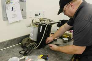 Dennis Dier, a service technician at Chris' Coffee, works on a Lamarzocco espresso machine in the service department on Wednesday, Feb. 10, 2021, in Latham, N.Y.  (Paul Buckowski/Times Union)