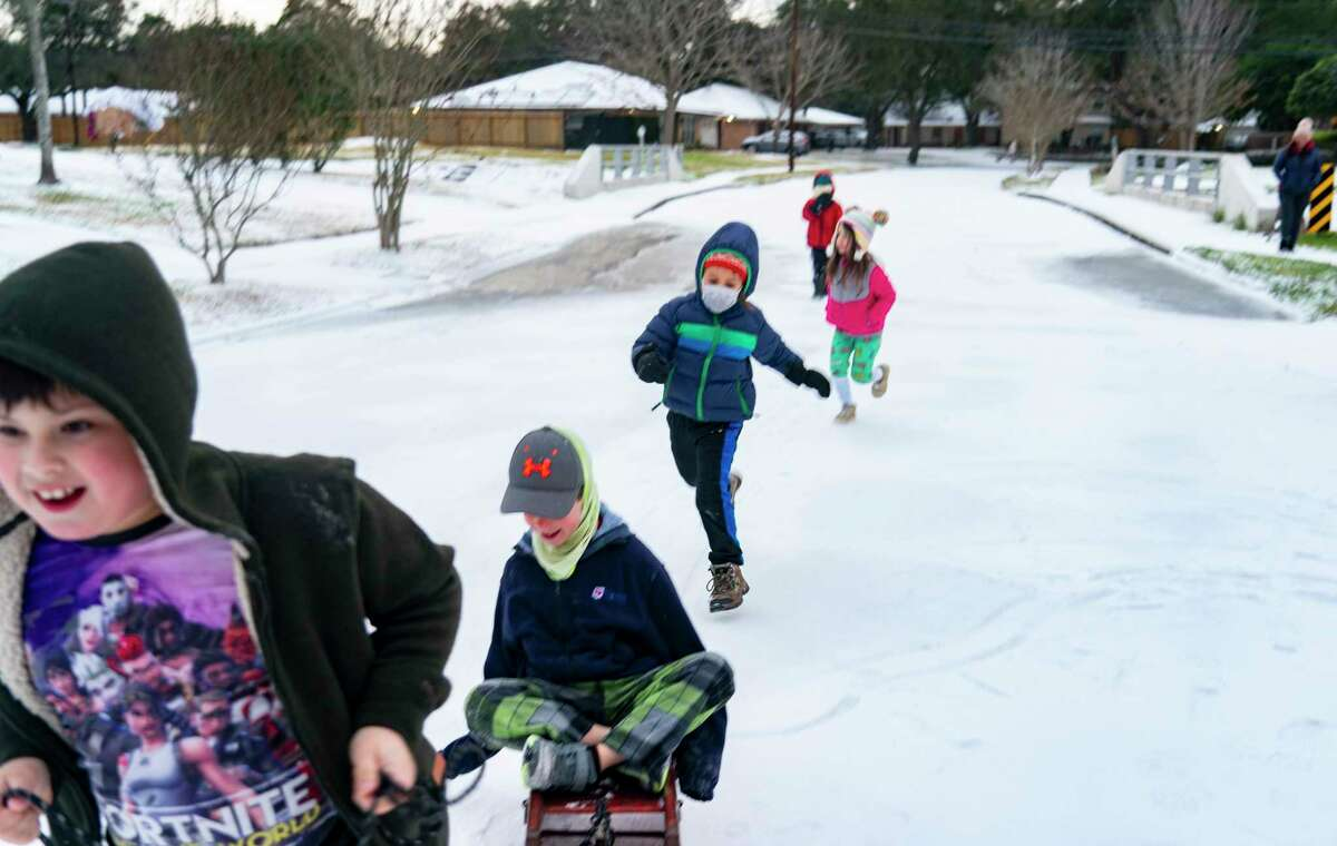 Neighbors play in the snow covered streets in the Westbury neighborhood, Monday, Feb. 15, 2021, in Houston.