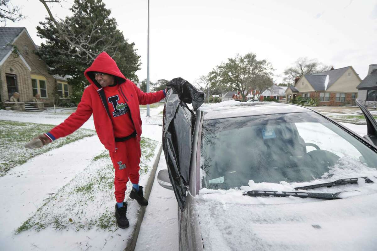 Jeranda Flowers tosses a chuck of ice as she removes plastic sheeting that covered her windshield of her car Monday in Houston.