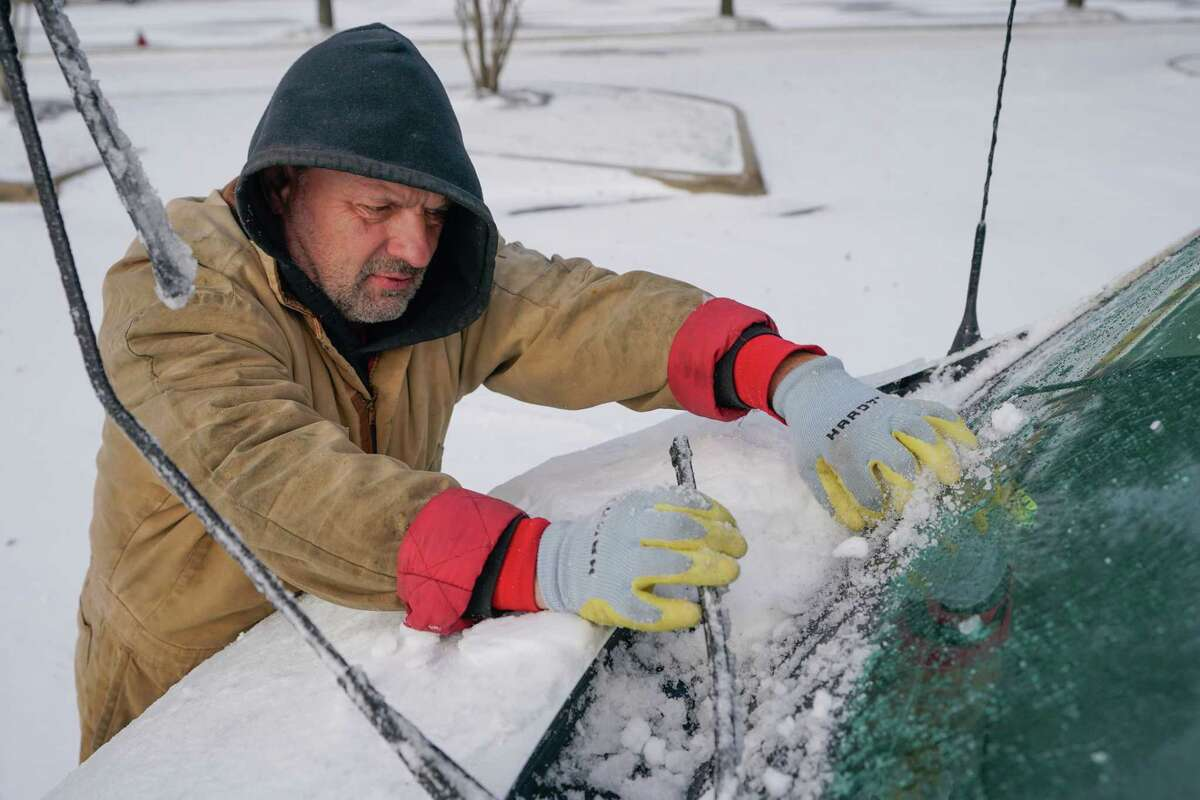 Tracey Jorgensen of Magnolia clears ice and snow from his windshield after driving along State Highway 249 during the arctic storm Monday, February 15, 2021 in Tomball.