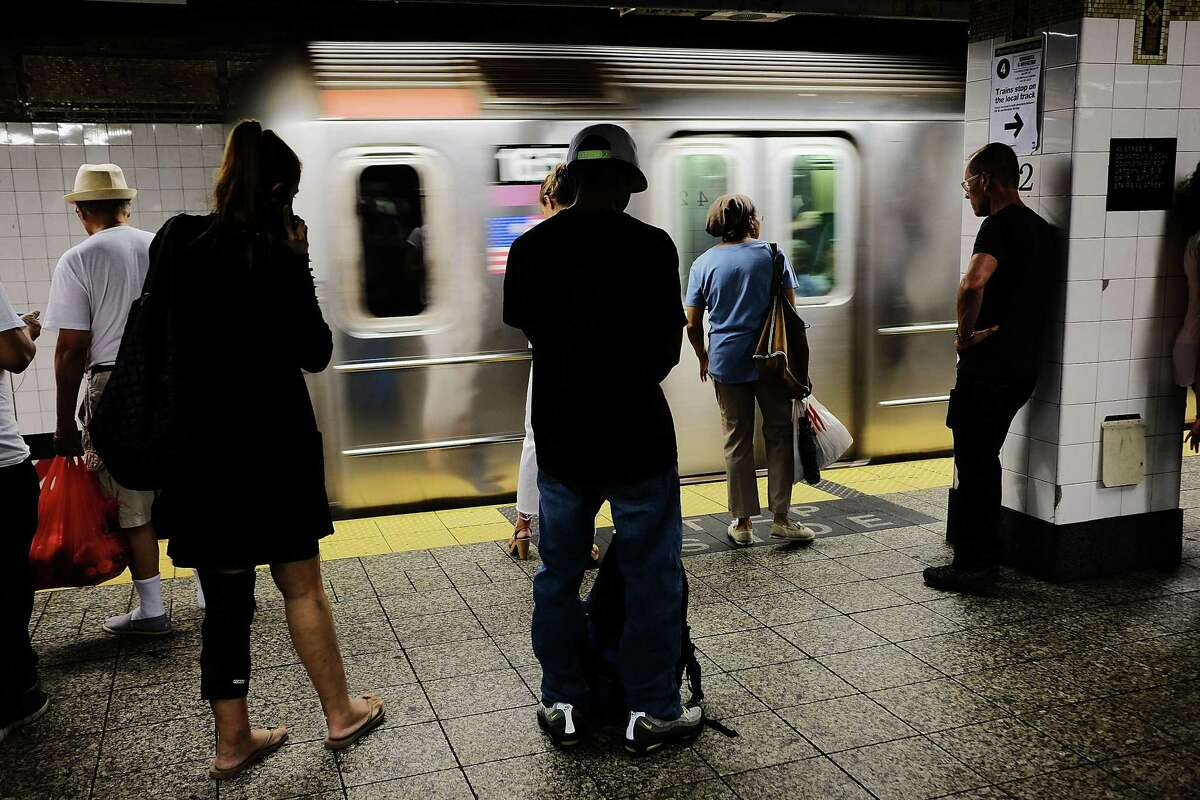 People wait for a Metropolitan Transportation Authority (MTA) subway to arrive in New York City.