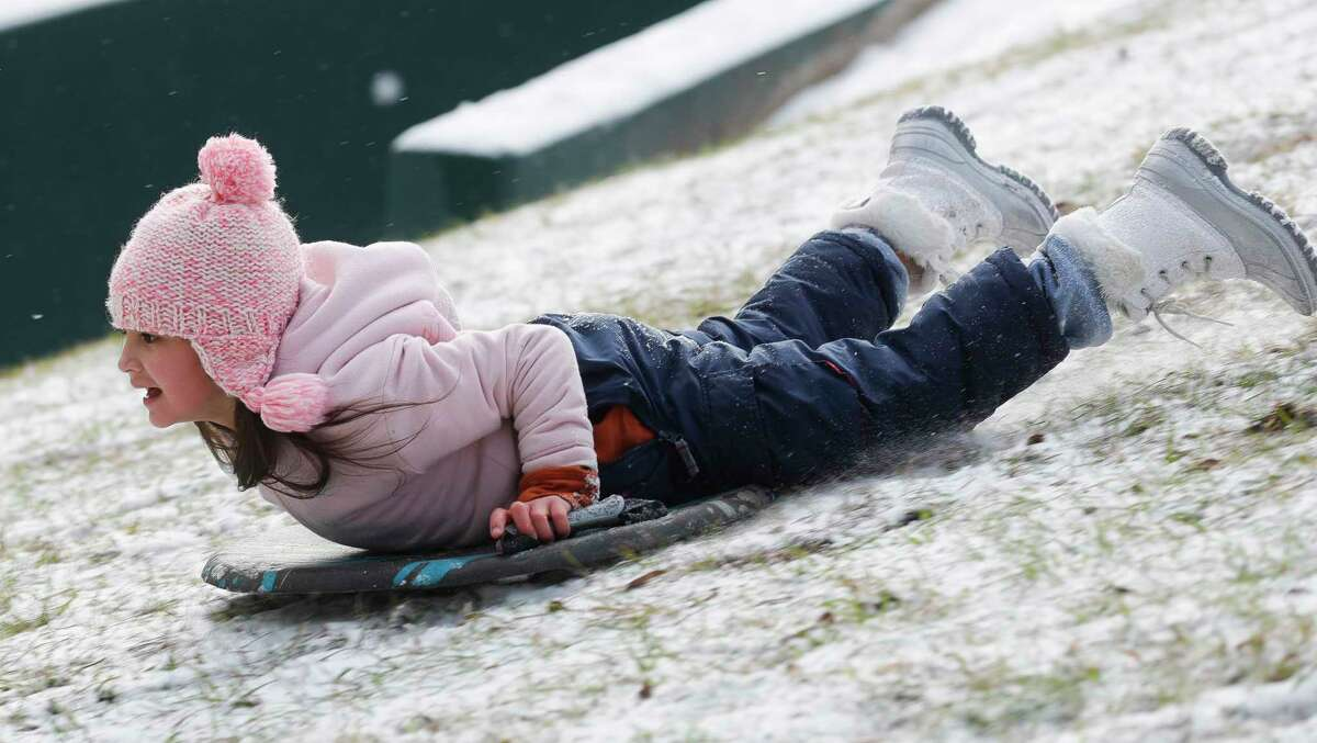 Zoey Bodkin slides down a hill after snow and ice covered the Greater Houston area, Monday, Feb. 15, 2021, in Kingwood.
