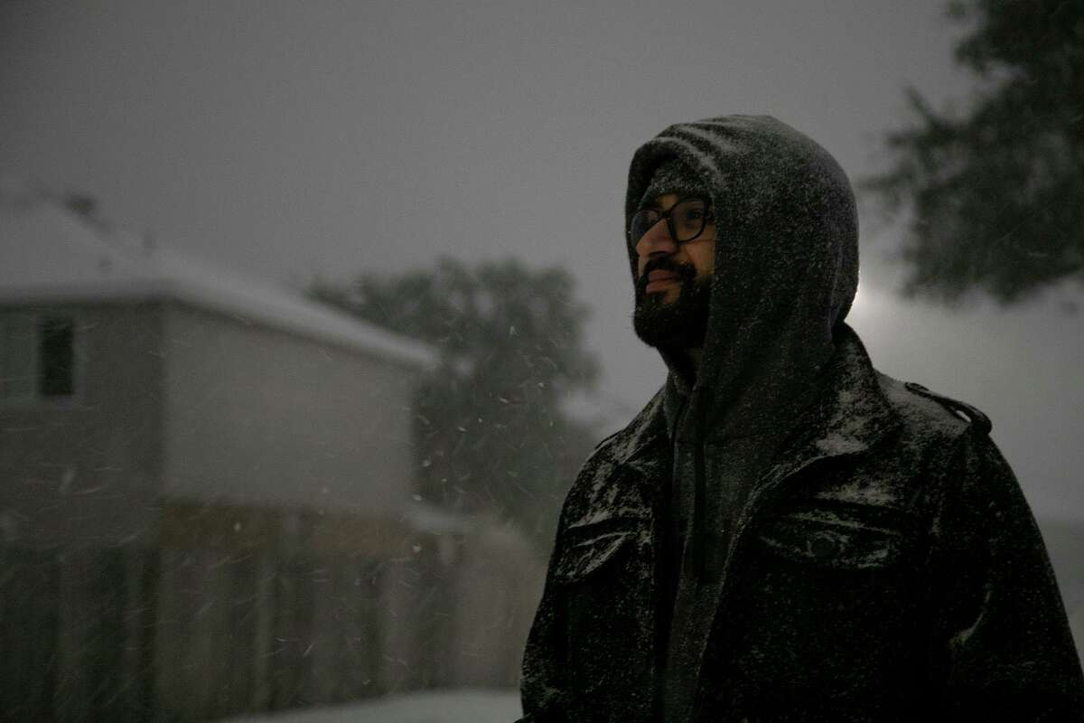 Umair Iqbal watches the snow fall early Monday morning, Feb. 15, 2021, in San Antonio.