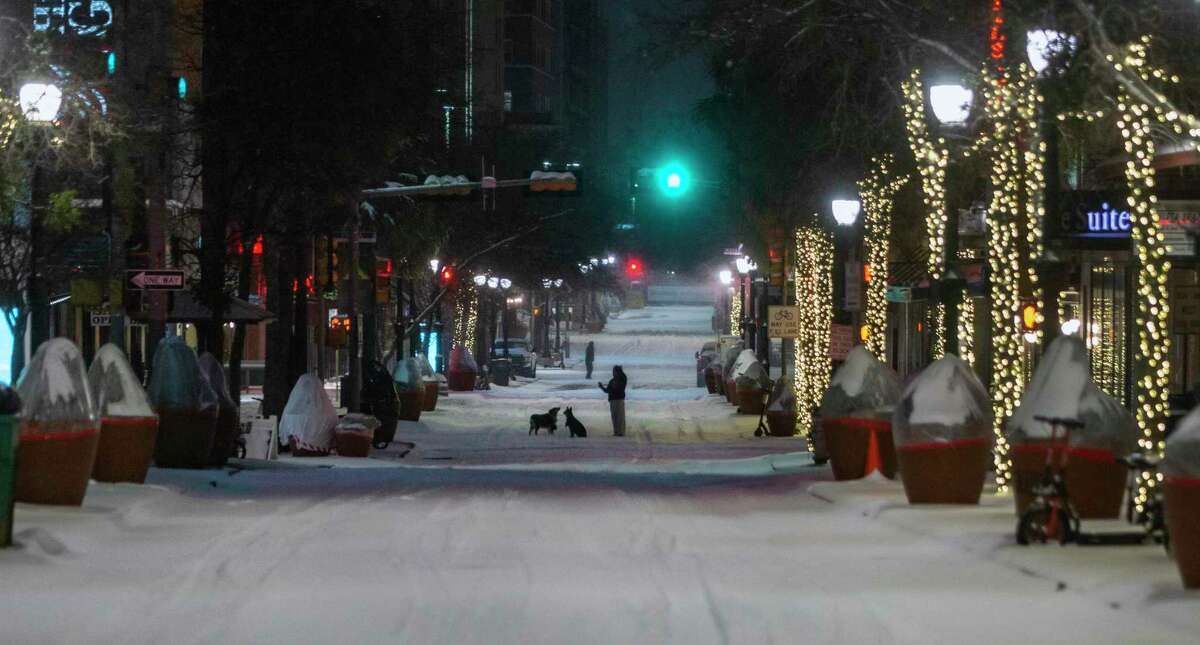 A person walks two dogs early Monday, Feb. 15, 2021, on a snow-covered Houston Street in downtown San Antonio. Overnight, 3 to 5 inches of snow blanketed the area.
