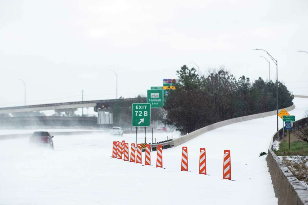 The north entrance of the Hardy Toll Road is blocked after the roadway was closed following an overnight snowfall Monday in Spring. Temperatures plunged into the teens Monday with light snow and freezing rain.