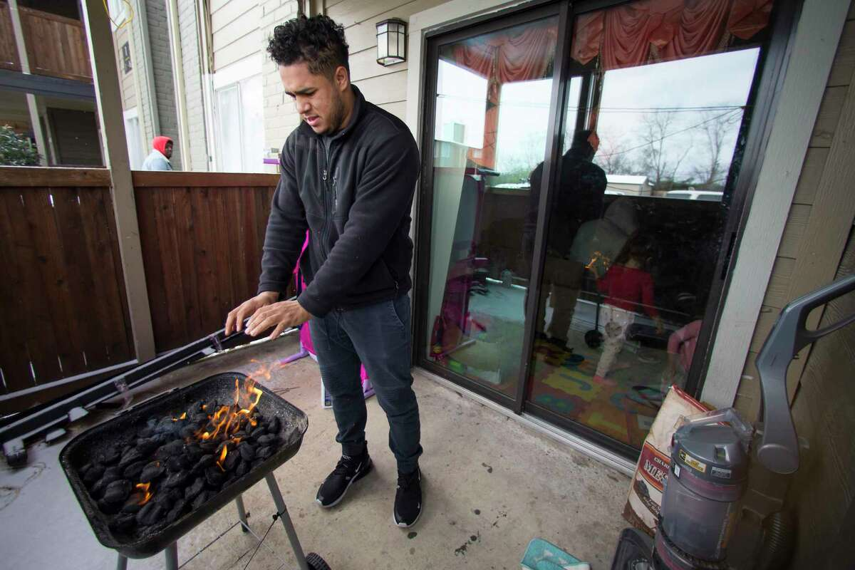 Kevin Morazan warms his hands after lightning his charcoal grill to cook after losing power due to rolling blackouts following an overnight snowfall in the Greenspoint area Monday, Feb. 15, 2021 in Houston. Temperatures plunged into the teens Monday with light snow and freezing rain. The stove in his apartment is electric.