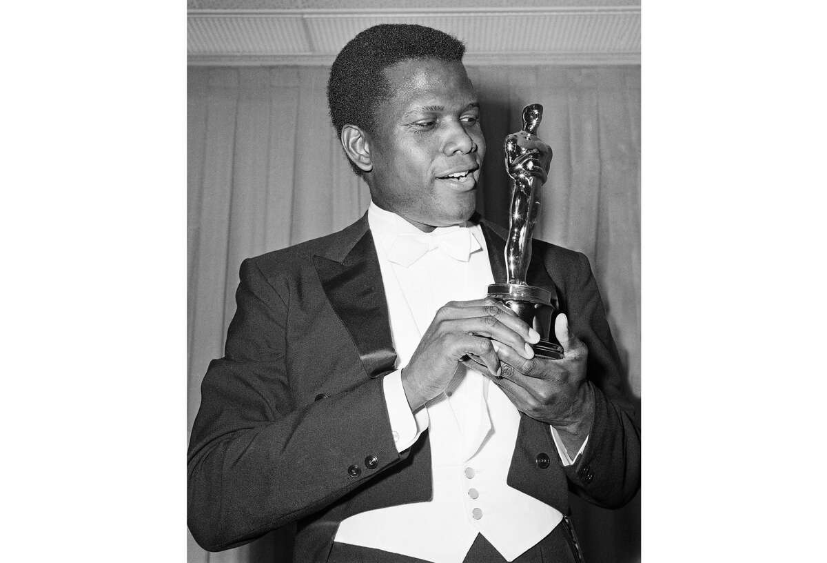 """Actor Sidney Poitier appears with his Oscar for best actor, for his role in """"Lillies of the Field,"""" at the 36th Annual Academy Awards in Santa Monica, Calif., on April 13, 1964."""