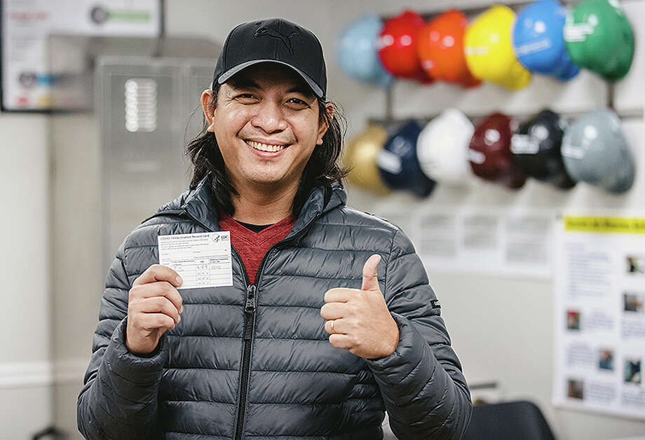A team member at JBS USA's Beardstown facility shows a COVID-19 vaccination card. Photo: Chris McGuire / © Chris McGuire Photography