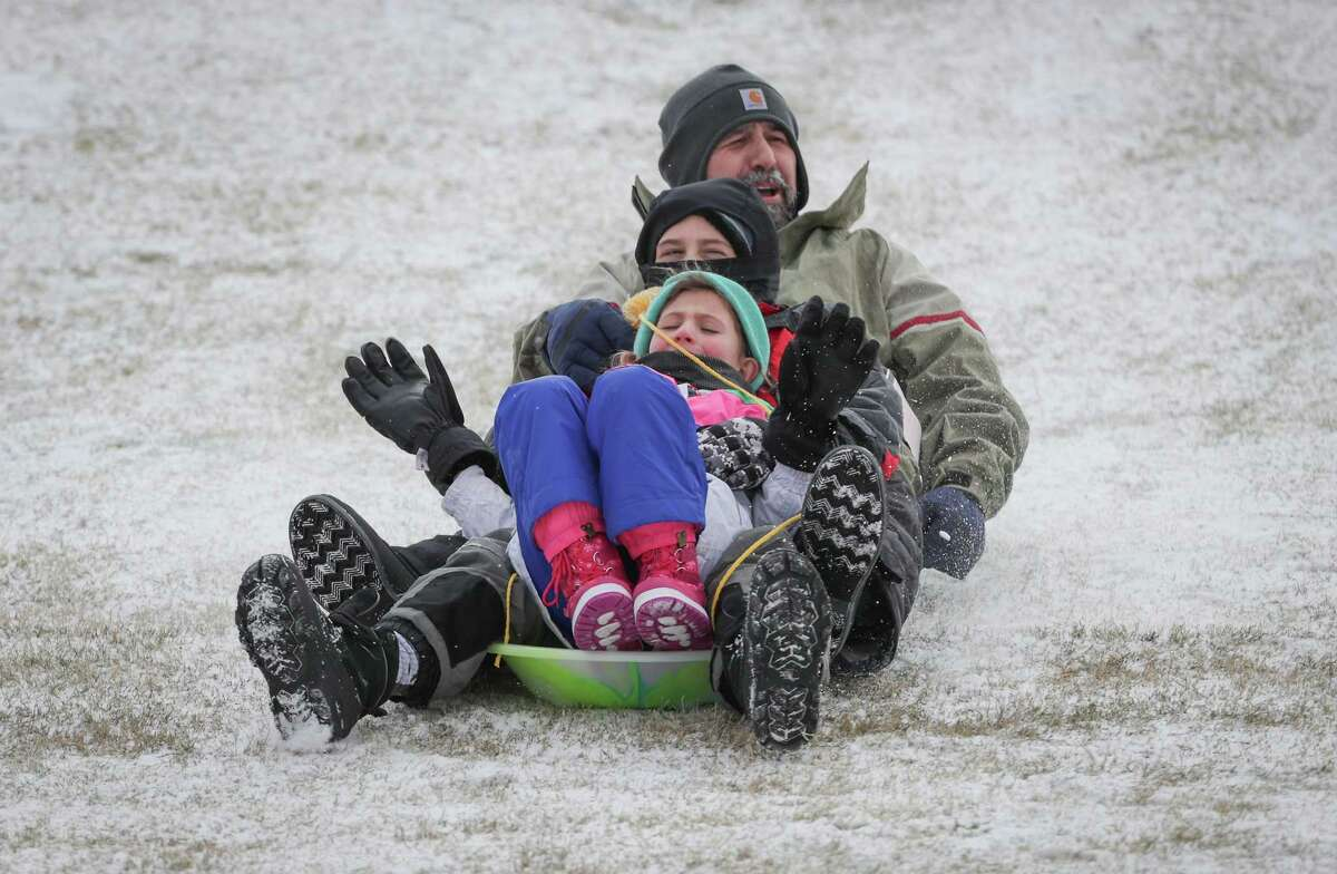 Fiona (front to back), Enzo and their father David DiPuma enjoy a sled ride on the Miller Outdoor Theatre hill Monday, Feb. 15, 2021, in Houston.