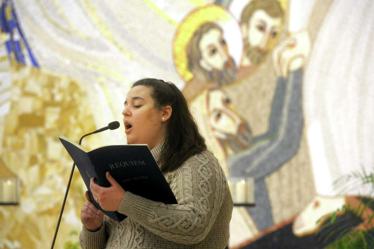 Student Michaela Vieira sings a hymn at the start of a COVID-19 memorial prayer service held in the Chapel of the Holy Spirit on the campus of Sacred Heart University, in Fairfield, Conn. Feb. 15, 2021.