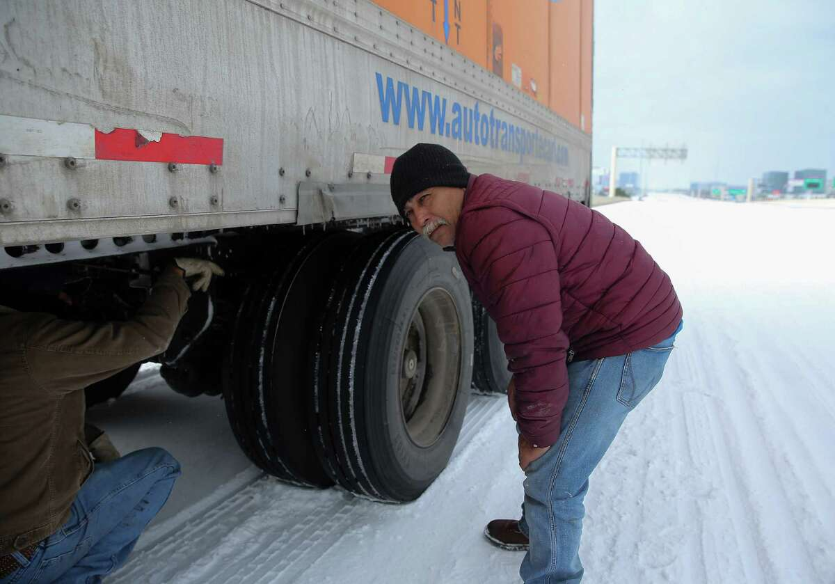 Daniel Del Rio, left, and Robert Barrientos try to fix their 18-wheeler that broke down on Interstate 10 eastbound due to the cold weather Monday, Feb. 15, 2021, in Houston.