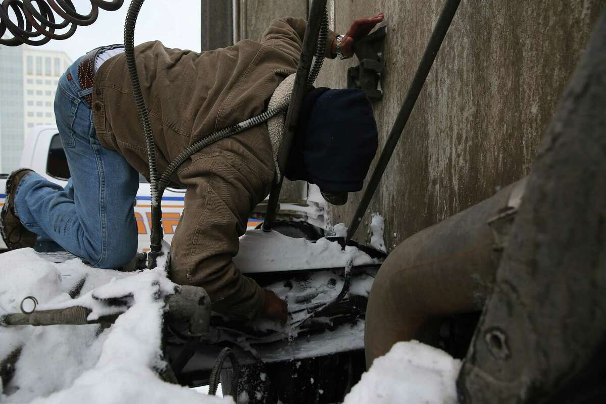 Daniel Del Rio tries to fix his 18-wheeler that broke down on Interstate 10 eastbound due to the cold weather Monday, Feb. 15, 2021, in Houston.