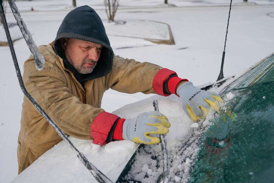 Tracey Jorgensen of Magnolia clears ice and snow from his windshield after driving along State Highway 249 during the arctic storm Monday, February 15, 2021 in Tomball. Photo: Melissa Phillip/Houston Chronicle / @2021 Houston Chronicle