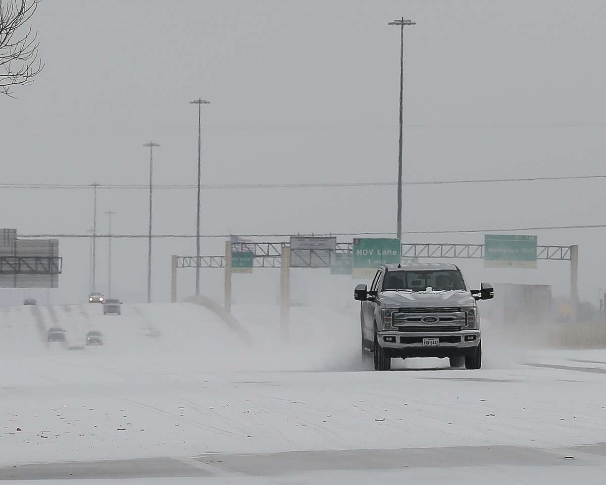 Vehicles driving on snow-covered Interstate 10 Monday, Feb. 15, 2021, in Houston.