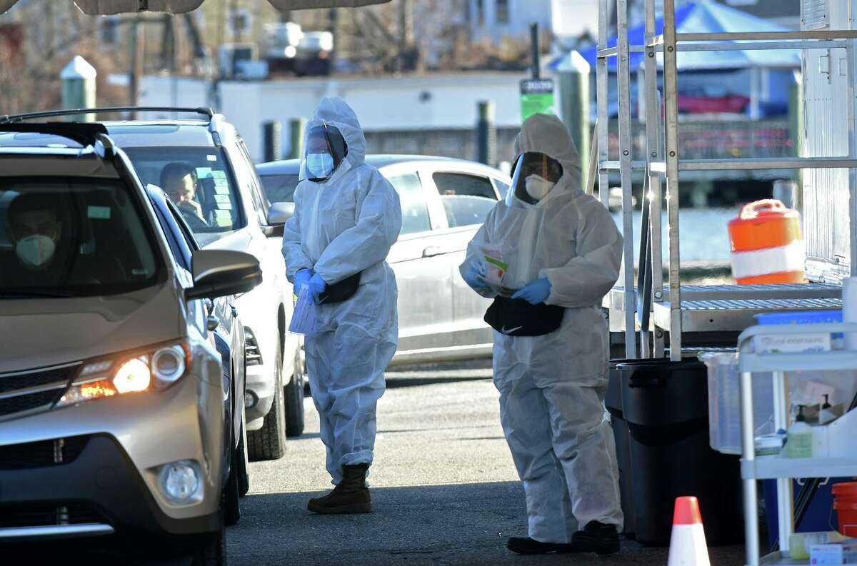 People get tested for COVID-19 at at a drive-through testing site in Norwalk.