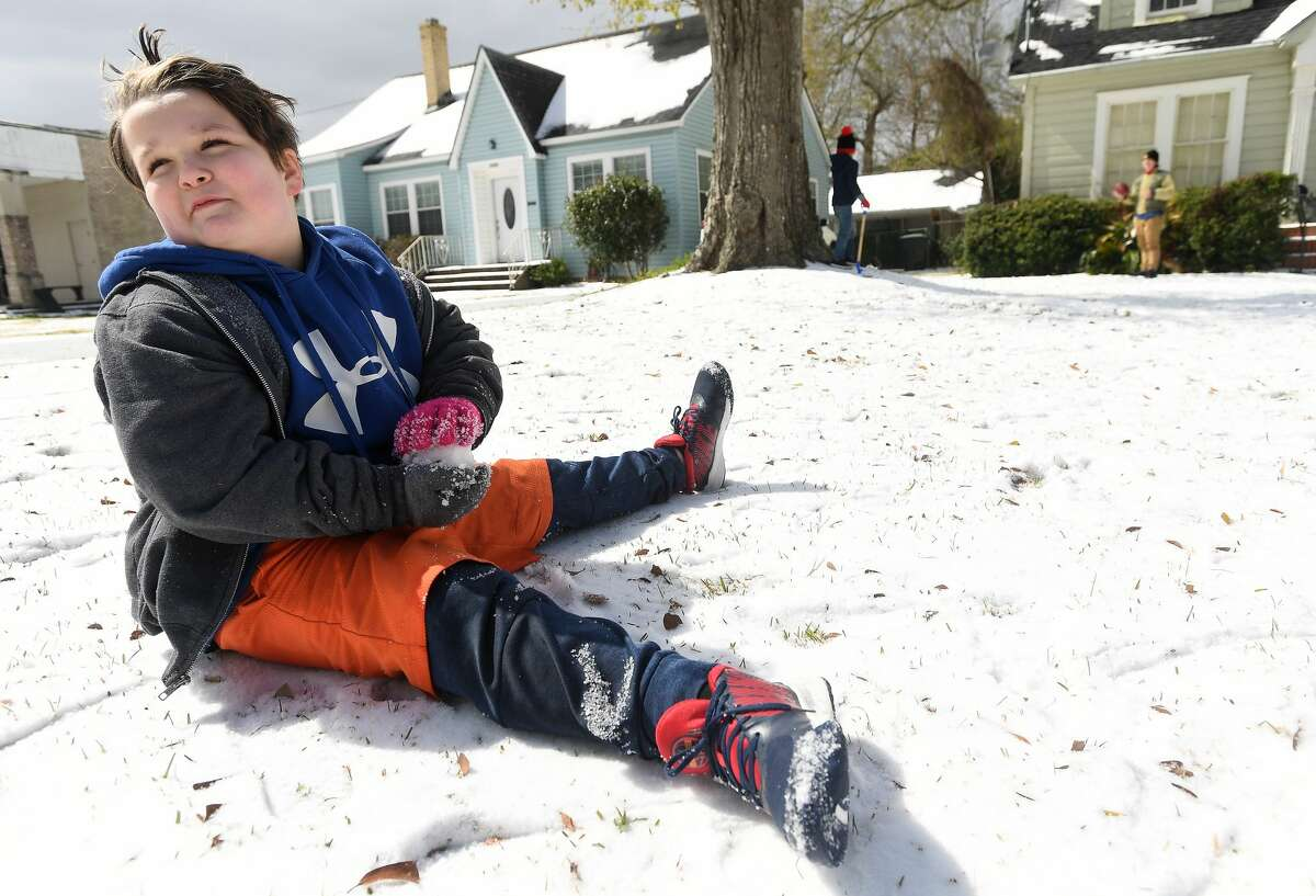 Lucas Trahan works on making a snowball from the layer of icy snow in his yard while playing outside with family and friends Monday. Photo taken Monday, February 15, 2021 Kim Brent/The Enterprise