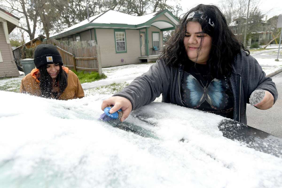 Jazmine Sanchez laughs as Daniela Uresti uses a spoon and small brush to try and scrape the ice from her vehicle as Southeast Texans awoke to frigid temperatures and iced cars and roadways Monday as the arctic front moved in overnight. Photo taken Monday, February 15, 2021 Kim Brent/The Enterprise