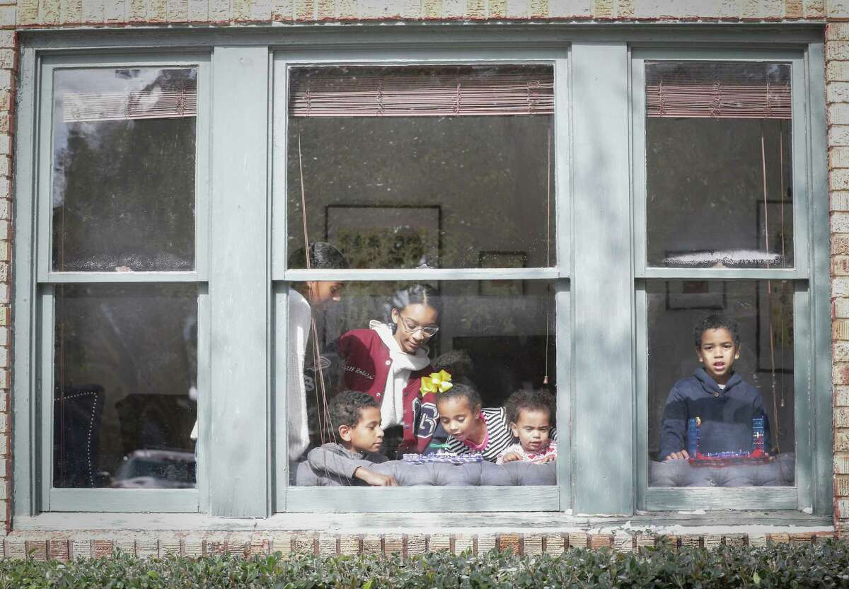 Ava Bocock (l-r), Richard Bocock, Elle Lewis, Catherine Bocock, Claire and Gregory Bocock stay warm playing in the sunlight of their front window during a power outage in Third Ward Monday, Feb. 15, 2021, in Houston.