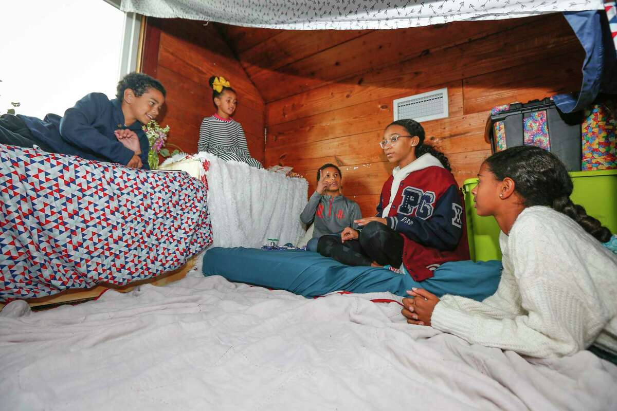 Gregory Block, Catherine Bocock, Richard Bocock, Elle Lewis and Ava Bocock stay warm in a fort they built in their third floor converted attic during a power outage in Third Ward Monday, Feb. 15, 2021, in Houston.