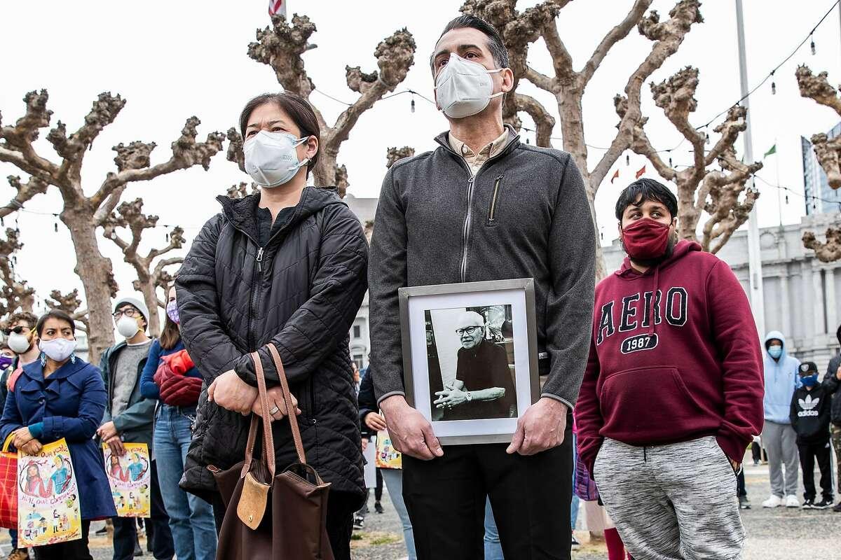 Relatives hold a photograph of attack victim Vicha Ratanapakdee at a rally at Civic Center Plaza on Sunday.