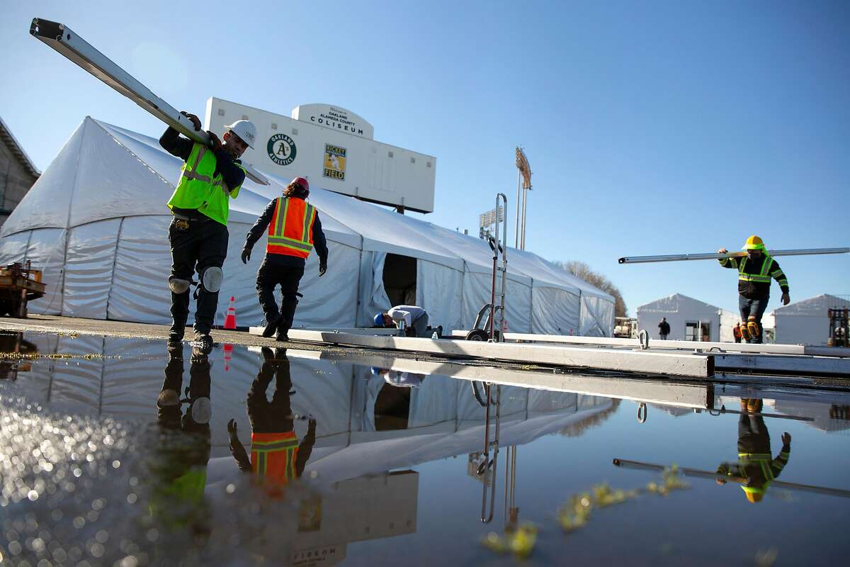 Workers build a mass vaccination site Friday at the Oakland Coliseum. The site opens Tuesday, a few days after S.F. announced it is temporarily closing two clinics over supply problems.