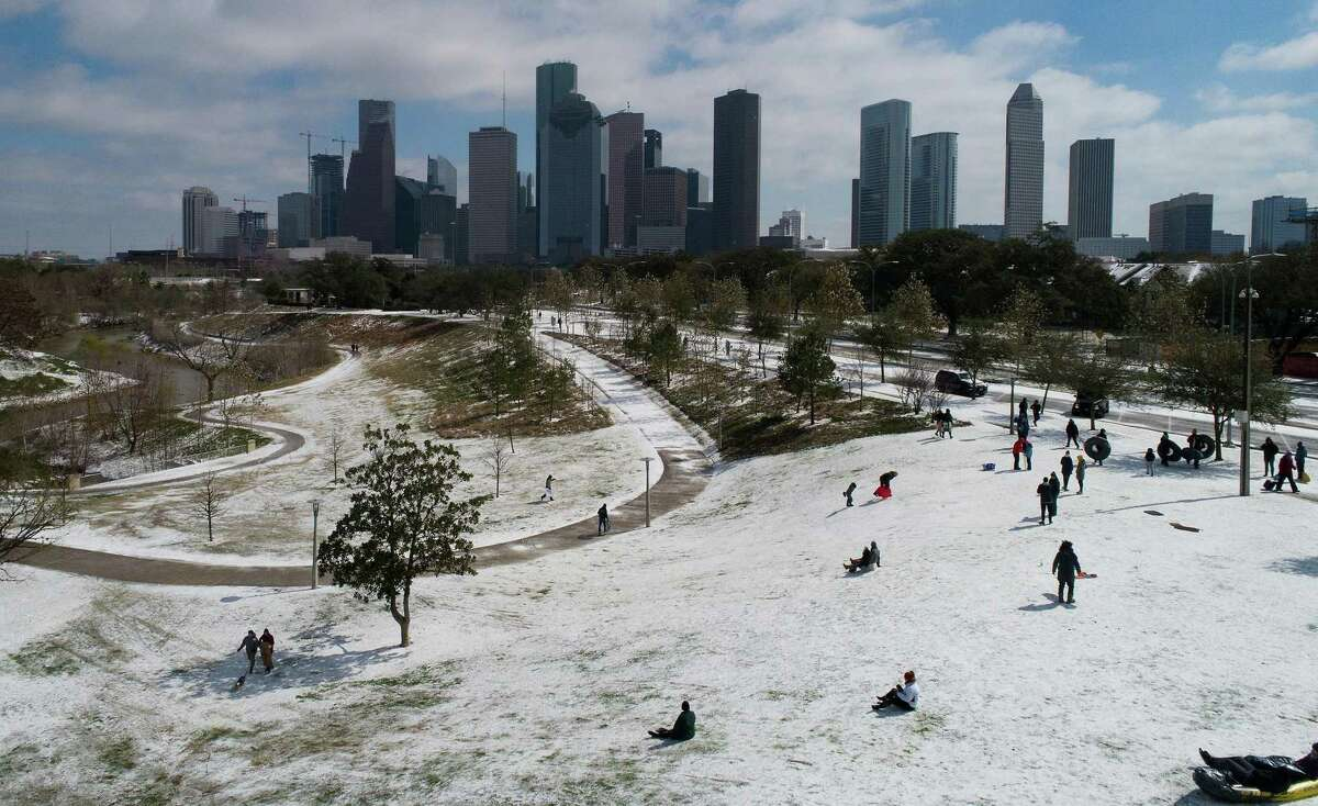 People take advantage of the rare snow and use whatever they can to sled at Buffalo Bayou Park in Houston on Monday, Feb. 15, 2021.