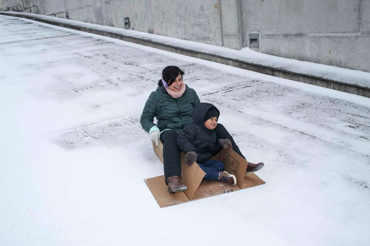 Toral Shah and her son Zavian, 3, slide down the ramp of a parking garage as a winter storm hits Houston on Monday, Feb. 15, 2021, at Carnegie Vanguard High School in Houston.