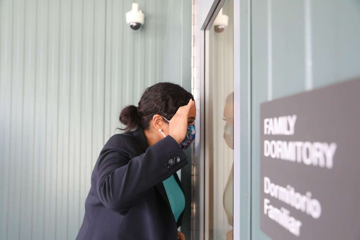 Mayor London Breed peeks through the glass doors into the family dormitory while touring the Bayview Safe Navigation Center.