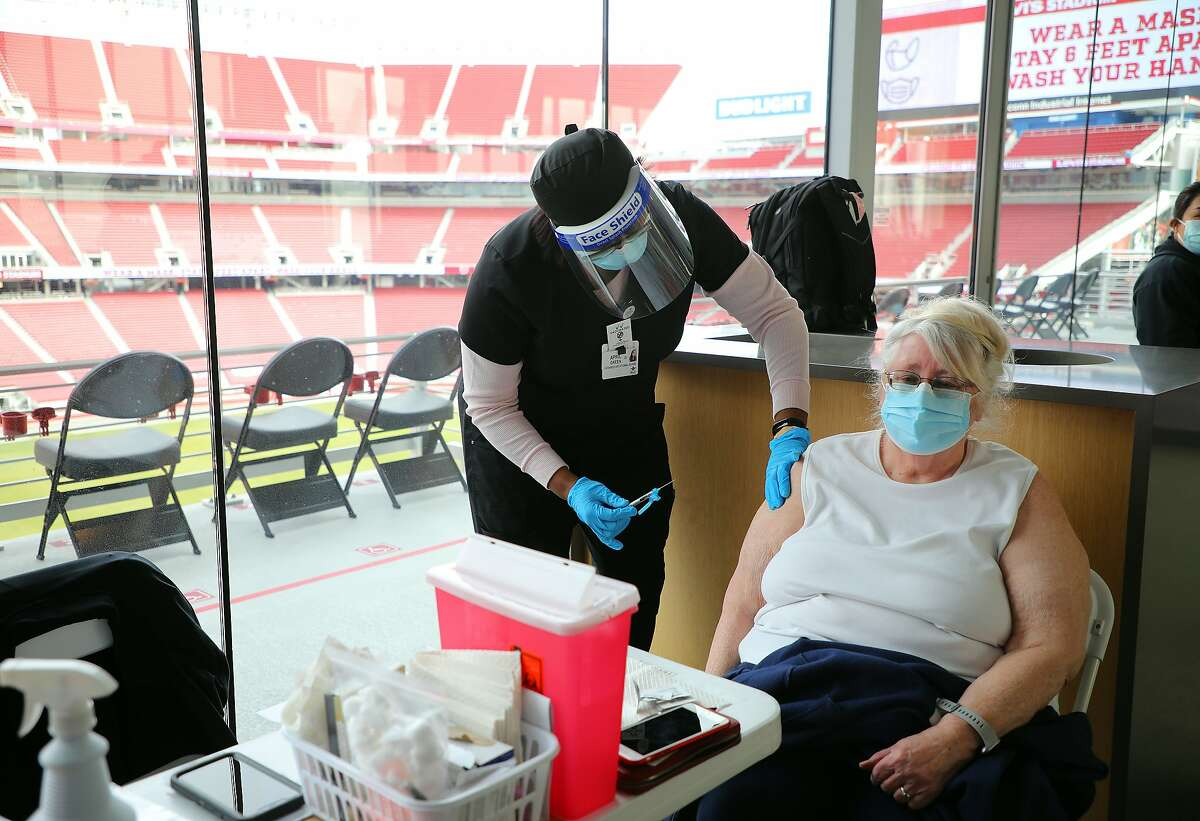 April Green, a nurse, administers a coronavirus vaccine at Levi's Stadium in Santa Clara, Calif., on Tuesday, Feb. 9, 2021. The United States, facing a growing threat from more contagious and possibly deadlier virus variants, is gradually administering more doses every day, now up to an average of about 1.7 million as of Sunday night, according to a New York Times database. (Jim Wilson/The New York Times)