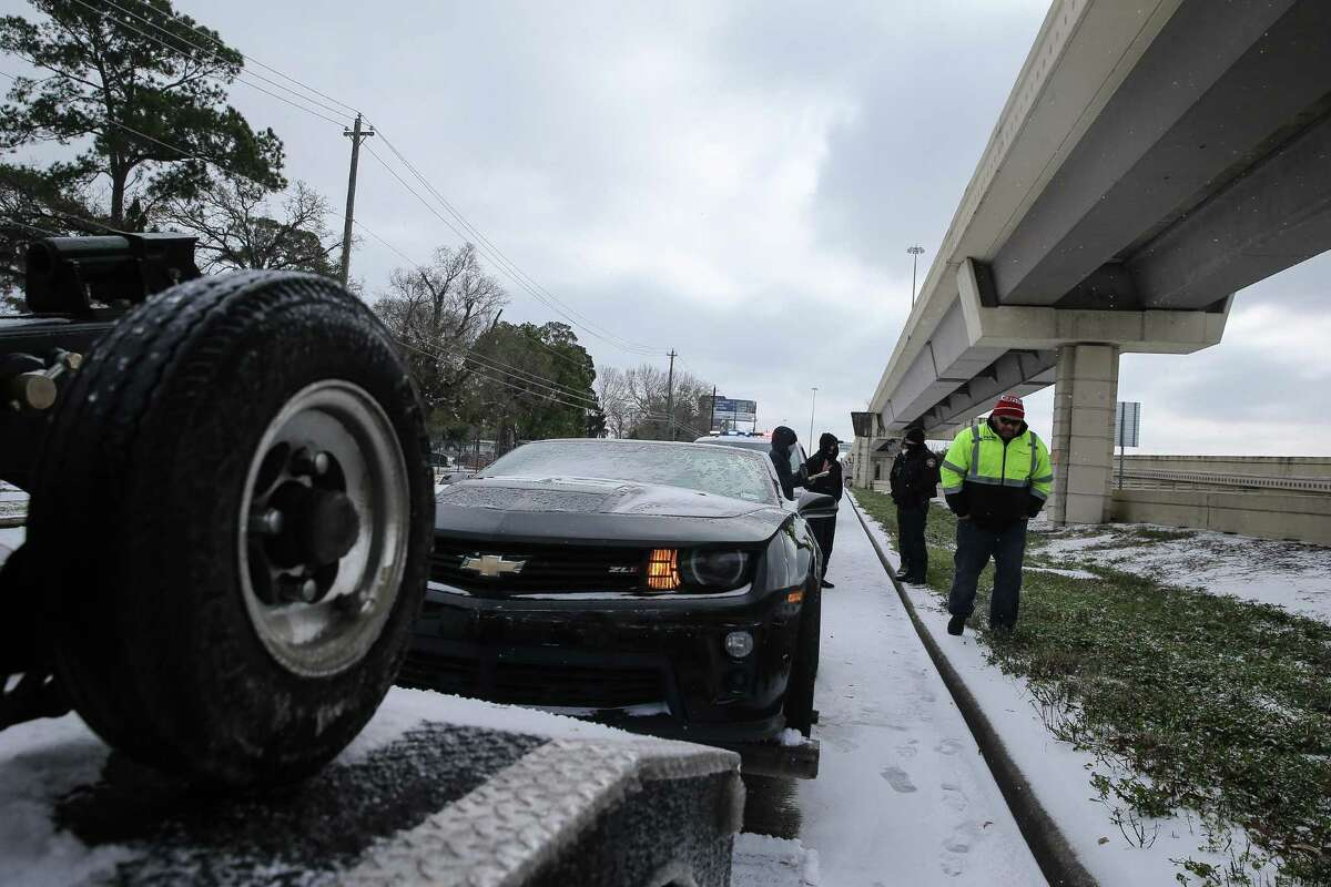 A Houston city tow truck is towing a car with electrical problems on Katy Freeway Monday, Feb. 15, 2021, in Houston.