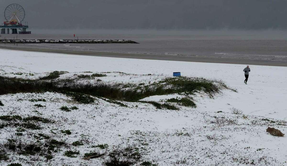A jogger run along the snow covered beach near 37th Street in Galveston, Texas on Monday, Feb. 15, 2021. (Jennifer Reynolds/The Galveston County Daily News via AP)