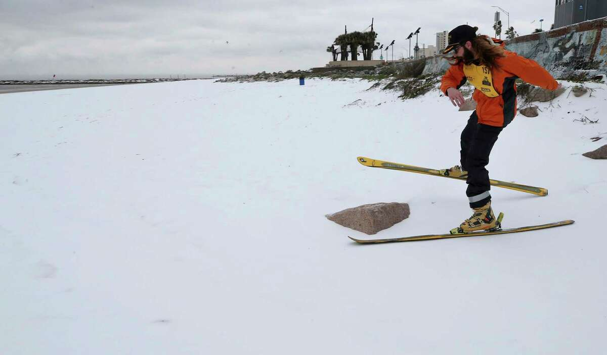 Sam Fagg skis on the beach near 45th Street in Galveston, Texas on Monday, Feb. 15, 2021, after an overnight winter storm covered the island in ice and snow. (Jennifer Reynolds/The Galveston County Daily News via AP)