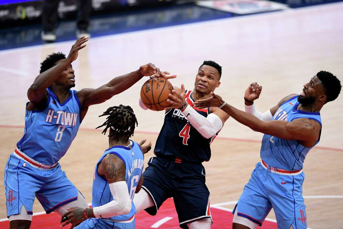 Houston Rockets forward Jae'Sean Tate (8), guard David Nwaba (2) and guard Ben McLemore (16) battle for the ball against Washington Wizards guard Russell Westbrook (4) during the first half of an NBA basketball game, Monday, Feb. 15, 2021, in Washington. (AP Photo/Nick Wass)