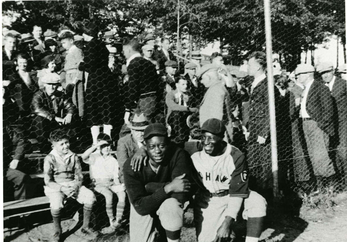 Two unidentified Mohawk Giants players, possibly pitcher Adolph Fleming and infielder Marcel Brooks, standing in front of the bleachers at Central Park in Schenectady, New York as the crowd fills them.